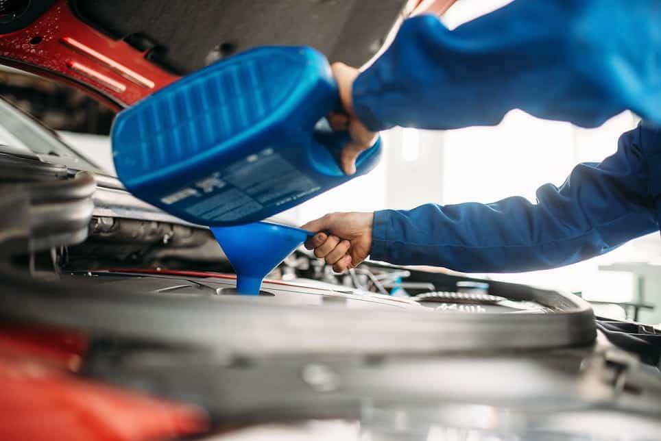 Technician change oil in the car engine. Vehicle motor maintenance, auto-service - Oil Change Maple Ridge