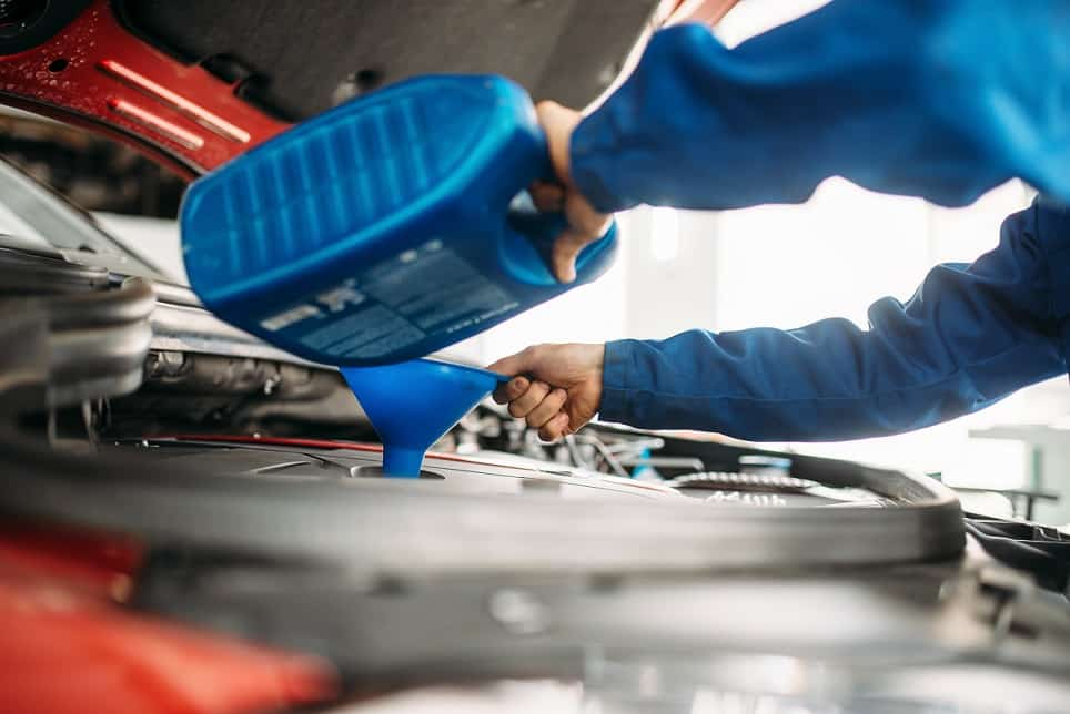 Technician change oil in the car engine. Vehicle motor maintenance, auto-service - Oil Change Maple Ridge